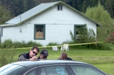 Detectives compare notes outside a house Tuesday in the Wolf Lodge area east of Coeur d'Alene where three bodies were found Monday night. They had been murdered. An Amber Alert has been issued for two children who lived in the home. Photo by Jesse Tinsley/the spokesman-review